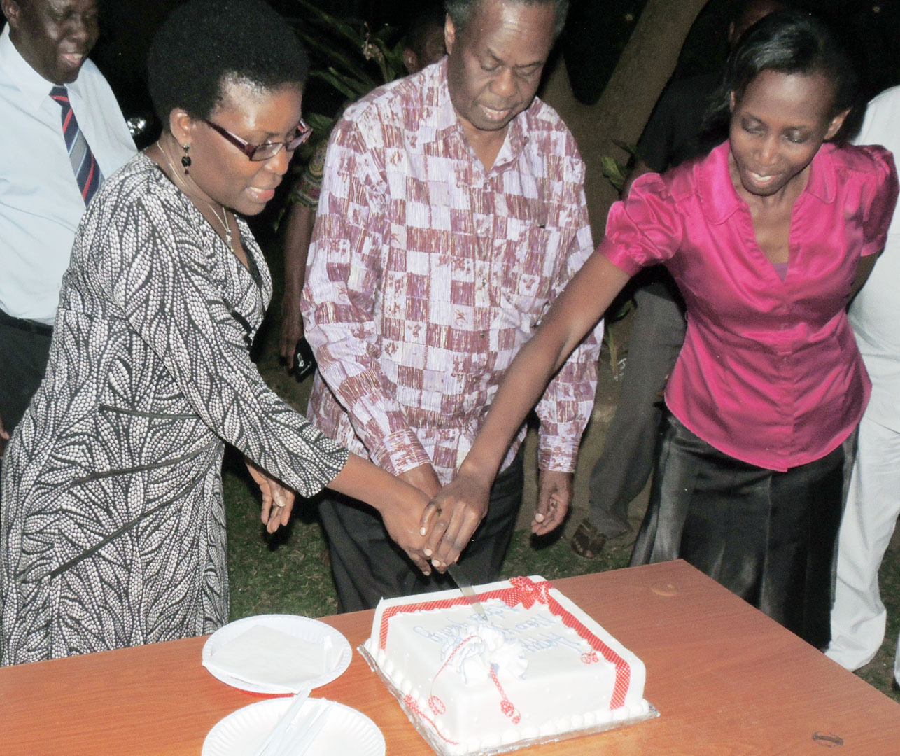Prof Francis Omaswa cutting the cake with Dr Elsie Kiguli-Malwadde left and Harriet Malinga right