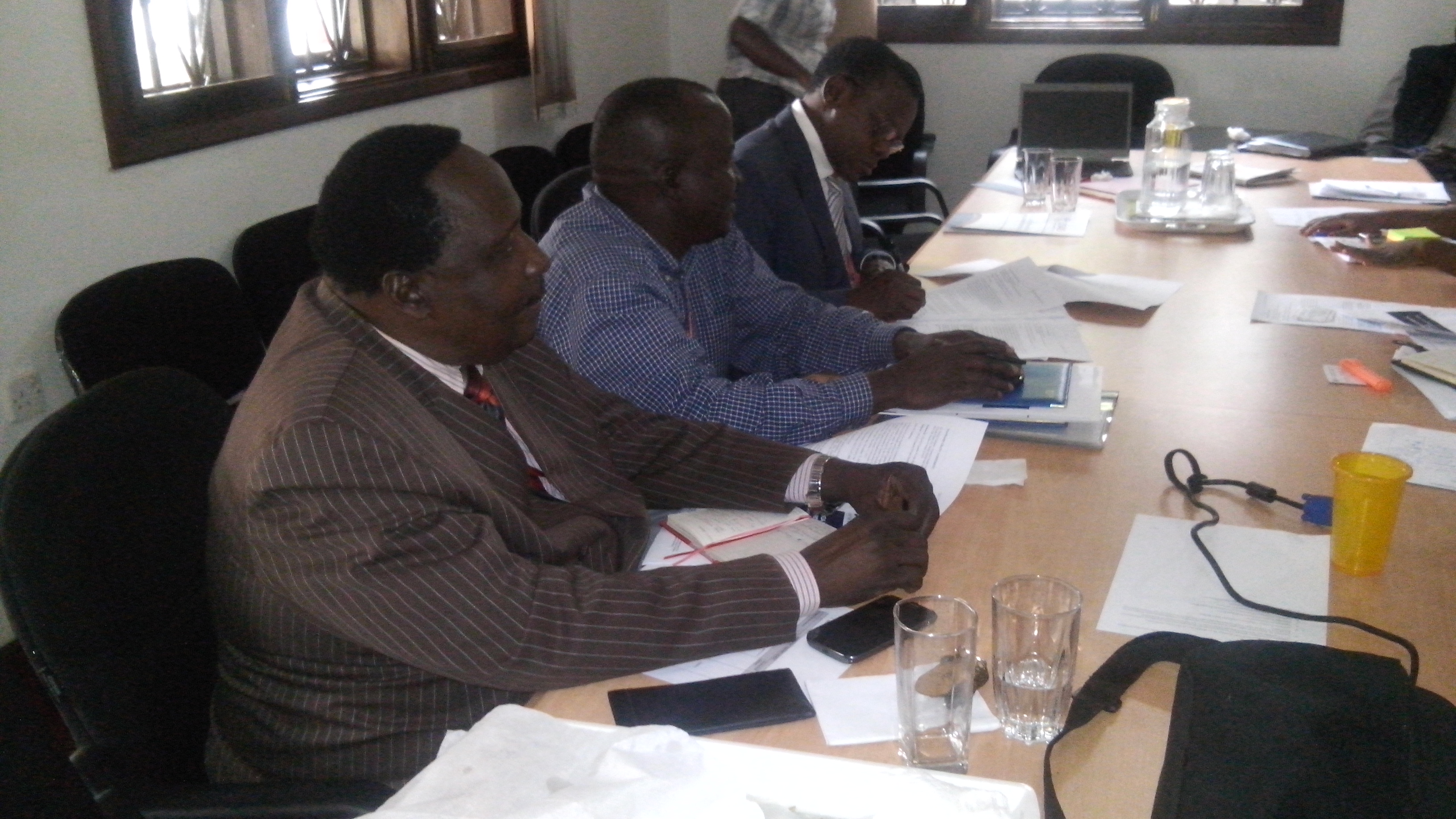 Right to Left  Dr.Patrick Kadama signs the Contract and looking on are Joseph Ogwapit and Dr.Peter Eriki