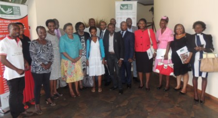 Participants pause for a photo during the press briefing in Kampala
